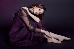 与大蓝眼睛的对比时尚亚美尼亚妇女poContrast时尚亚美尼亚妇女画象坐在紫色的黑暗的背景 库存照片