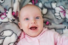 与大蓝眼睛的滑稽的惊奇的笑的孩子 库存图片