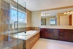与大虚荣内阁、玻璃客舱阵雨和白色浴盆的豪华卫生间内部 免版税库存图片