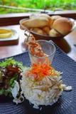 与大虾串的新鲜的棕榈沙拉在与温暖谋生的一块玻璃在背景中 库存照片
