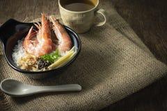 与大虾和姜混合的米稀饭,薤切片和被油炸的大蒜和黑胡椒在黑碗 茶放回 免版税库存图片