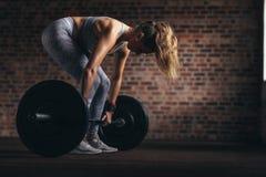 与大量的重量的坚定的健身妇女训练 免版税库存图片