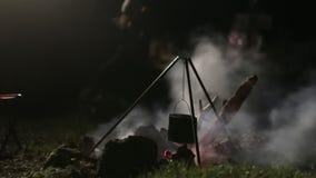 与大锅的营火在晚上 对火的男孩奔跑 影视素材