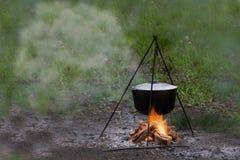 与大锅金属罐水壶的室外国家边烹调烹调的室外在自然中间在与的阵营附近 图库摄影