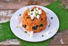 与大麦的粒、橄榄、蕃茄、春天葱和希腊白软干酪的膳食在绿色布料的白色板材在土气桌上 免版税库存照片