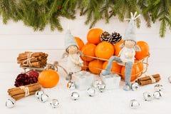与天使、蜜桔和桂香的圣诞节背景 库存照片