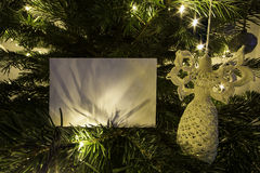 与天使玩具的空白的圣诞卡在圣诞树 免版税图库摄影