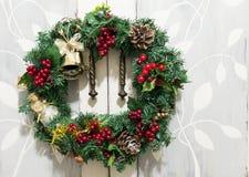 与天使的圣诞节在土气背景的花圈和响铃 免版税库存照片