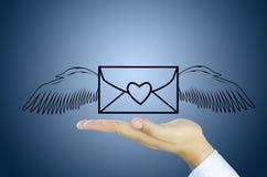 与天使翼的邮件在人的手上 免版税库存照片