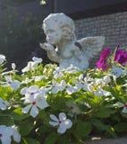 与天使雕象的花卉大农场主 库存图片