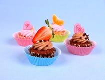 与天使,心脏,蜜桔,草莓的四块开胃杯形蛋糕 免版税库存照片