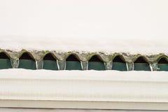 与天沟的积雪的冰冷的屋顶突出物在解冻以后 免版税库存照片