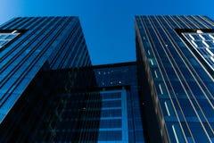 与天空的现代玻璃skycrapers背景和云彩反射和城市 免版税库存照片