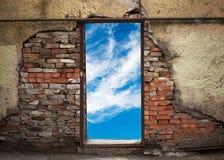 与天空的空的门道入口在老砖墙 库存图片