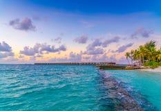 与天空的美好的日落在风平浪静在热带马尔代夫是 库存图片