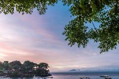 与天空的美好的日落在风平浪静在热带巴厘岛,印度尼西亚 库存照片