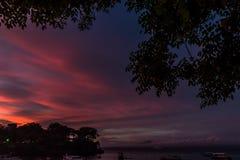 与天空的美好的日落在风平浪静在热带巴厘岛,印度尼西亚 免版税库存图片