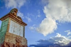与天空蔚蓝和云彩的老柱基路标 免版税库存照片
