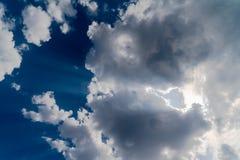 与天空蔚蓝和太阳的白色云彩通过云彩发光 免版税库存照片
