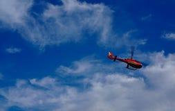 与天空蔚蓝和白色云彩的红色直升机飞行在背景中 免版税库存图片