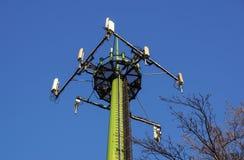 与天线的钢电信塔在蓝天和树 免版税库存图片