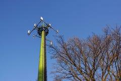 与天线的钢电信塔在蓝天和树 免版税图库摄影