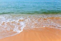 与天蓝色的泡沫似的海浪的黄色含沙海岸线在一个明亮的晴天 免版税图库摄影