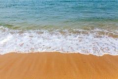 与天蓝色的泡沫似的海浪的黄色含沙海岸线在一个明亮的晴天 免版税库存图片