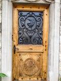 与天鹅铁加工的样式的美丽的木门在老房子在格律耶尔村庄,弗里堡小行政区,瑞士,欧洲 库存照片