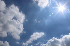 与太阳云彩和透镜火光的中间天天空蔚蓝 库存照片
