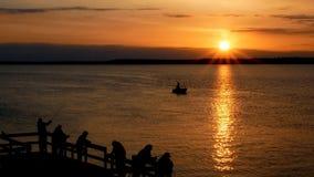 与太阳光芒的华美的日出在有剪影的湖人钓鱼 股票视频