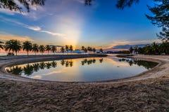 与太阳光芒的天空蔚蓝在海滩的日落期间 库存照片