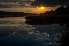 与太阳光芒的日落在河 巨大反射在与芦苇植物的水中 图库摄影