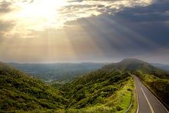 与太阳光芒的美好的日落在山和一条路的等高沿山的上面在背景  库存图片