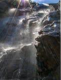 与太阳光芒的陡峭的岩石瀑布 库存图片