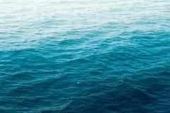 与太阳反射的深刻的蓝色海水波浪suface 图库摄影