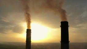 与太阳对比,有一股大管子厚实的白色烟的工业区从工厂管子倾吐 股票录像