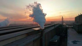 与太阳对比,有管子厚实的白色烟的工业区从工厂管子倾吐 污染  股票录像