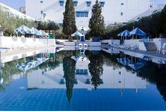与太阳床和蓝色伞的公开游泳池 图库摄影
