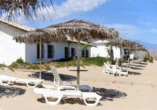 与太阳床的一张照片和在一个美丽的离开的海滩的伞 免版税库存图片