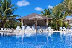与太阳懒人和一个酒吧的游泳池视图在古巴 库存图片