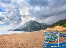 与太阳懒人和遮光罩的离开的海滩 库存图片