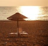 与太阳懒人的梦想的海滩在落日的遮阳伞下 免版税库存照片