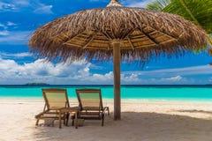 与太阳懒人的梦想的海滩 免版税库存照片