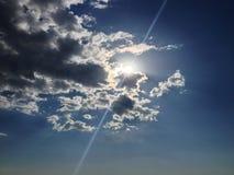 与太阳火光的蓝天通过云彩 免版税库存照片