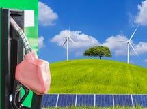 与太阳电池板和偏僻的树的燃料喷嘴服务站和在绿色领域的风轮机 库存图片