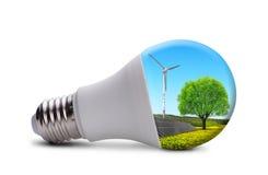 与太阳电池板和风轮机的Eco LED电灯泡 免版税图库摄影