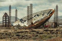 与太阳电池板的巨大的抛物面盘 生产的被放弃的建筑enegy 使用为甲醇和煤炭的生产 El 免版税库存照片