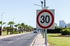 与太阳电池板的限速标志在有棕榈树的路在一个夏日 限速是在石渣路的30 km h 免版税库存照片