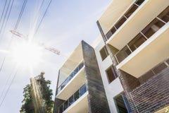 与太阳的现代大厦通过起重机发出光线 库存照片